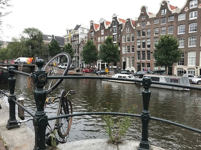 A bike hanging over the railing at the canals